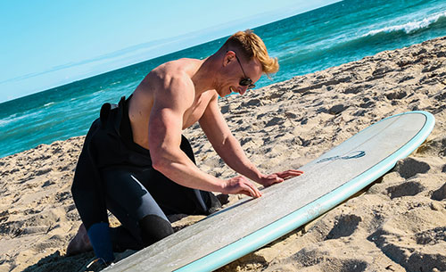 surfer cleaning a surfboard