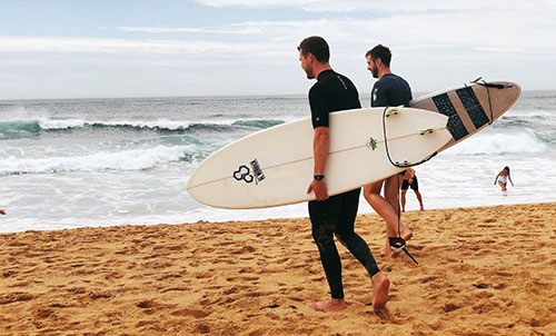 surfers going out into the ocean with their surfboards