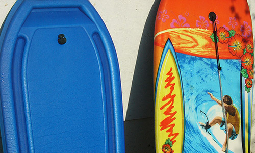 two bodyboards resting on the wall