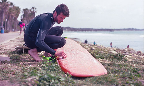 surfer applying base coat and wax on a surfboard