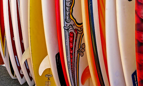 variety of different color and sized surfboards