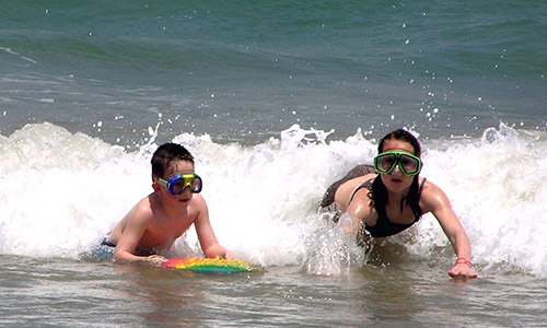 kids surfing and swimming with goggles on