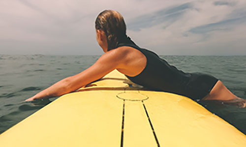 woman laying on top of a surfboard